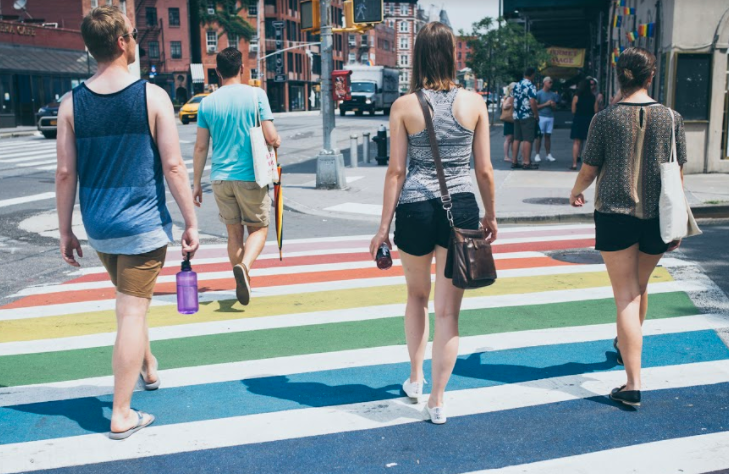 LGBTQ walking tour company in NYC taking a group across the Stonewall Inn's rainbow crosswalk
