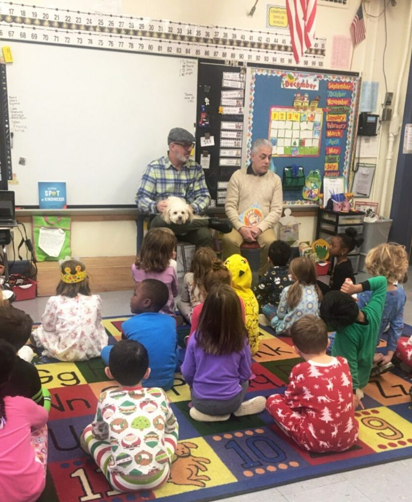 "Larry, Zane, and James reading ""Zane to the Rescue"" to schoolchildren"